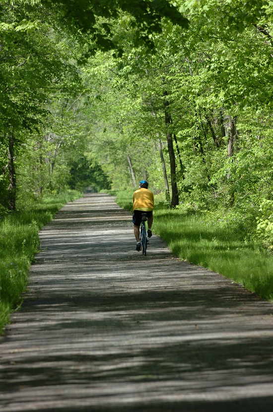 lone cyclist on paved greenway trail