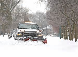 truck plowing snow on a tree lined street